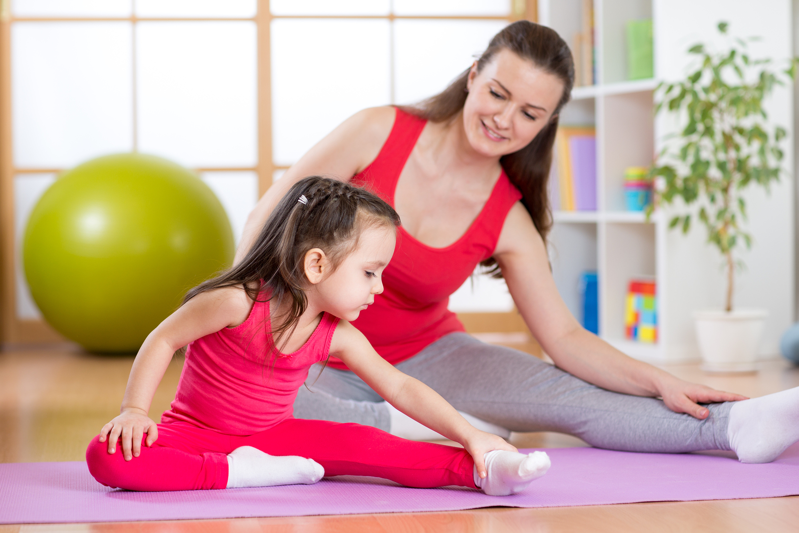 Mother and daughter doing fitness exercises on mat at home - Go Mommy